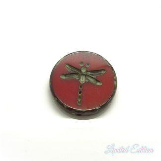 Deze rode platte kraal met een libelle erop is te koop bij kralenwinkel Limited Edition in Den Haag.