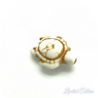 Deze synthetische howlite schildpad kraal is te koop bij kralenwinkel Limited Edition in Den Haag in de kleur wit.